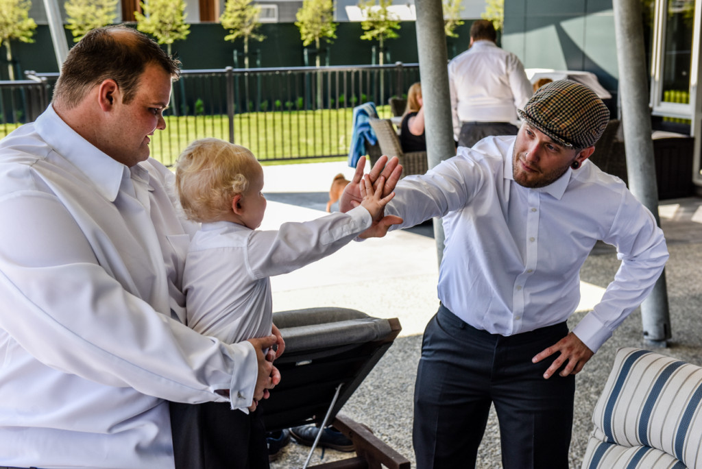 The mini groomsman high fives a guest