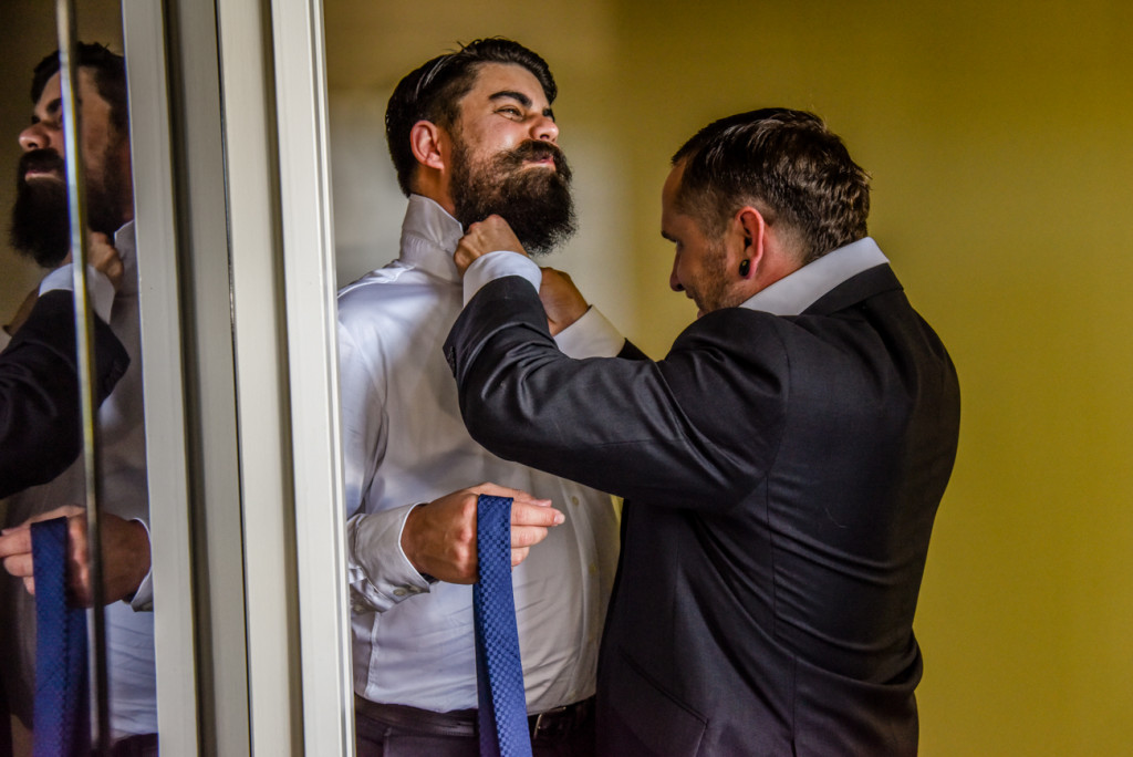 One of the groomsmen helping another groomsman suit up