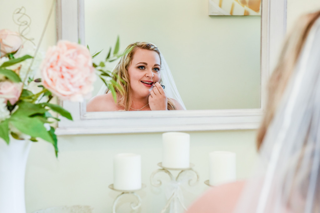 Bride looking at her reflection as she puts her lipstick on