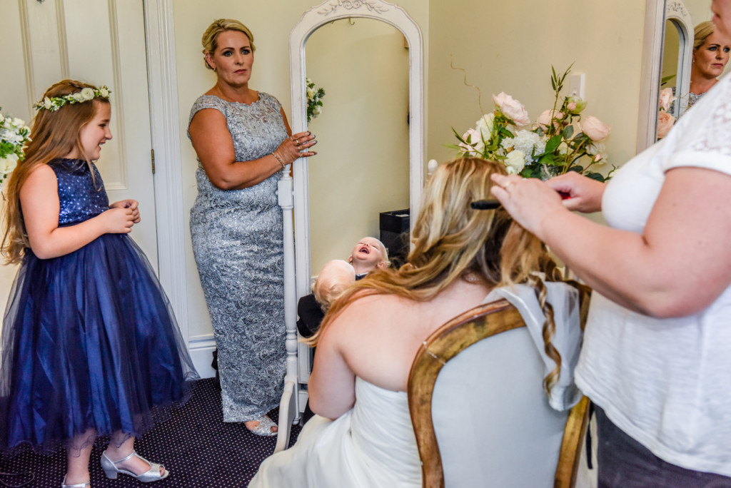Bridesmaid showing the bride a mirror while her hair is done by the family hairdresser