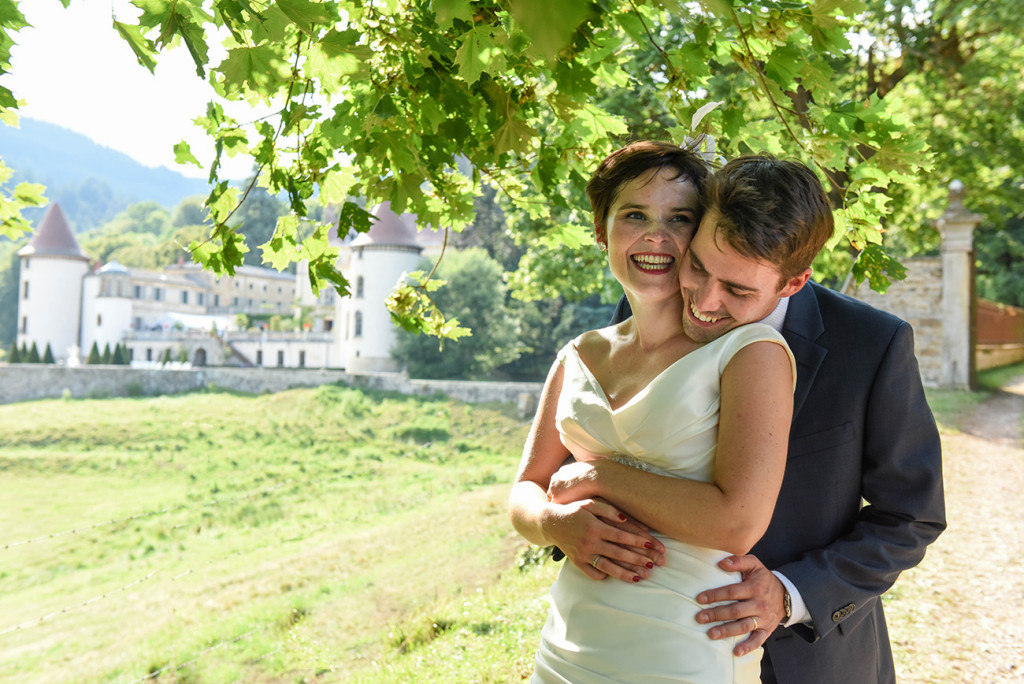 Bride and groom laugh at photoshoot at their outdoor French Wedding in Pranemoux Castle France French photographer