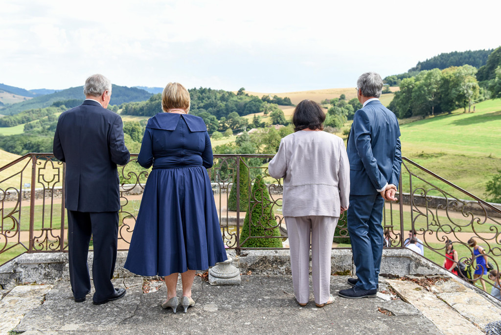Parents of the French couple overlooking the garden square in the French wedding Pranemoux Castle France