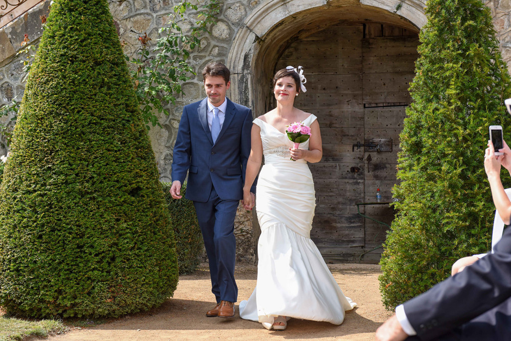 The French couple walking to the altar at their French wedding in Pranemoux Castle France