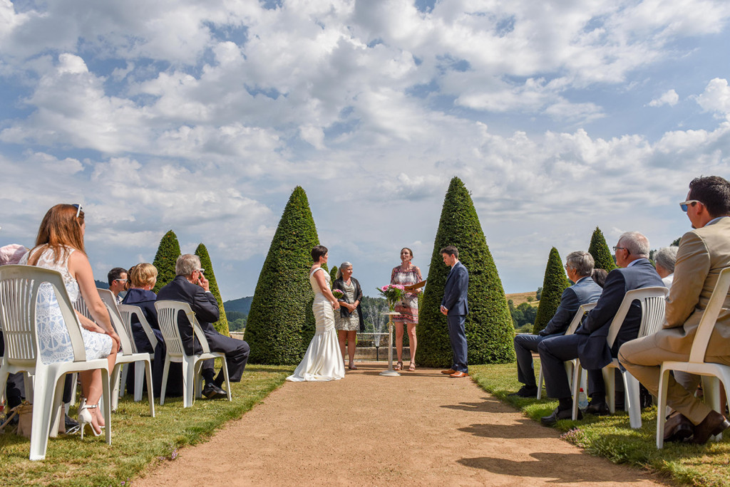 The American-French couple exchanging vows at their outdoor wedding in Pranemoux Castle France