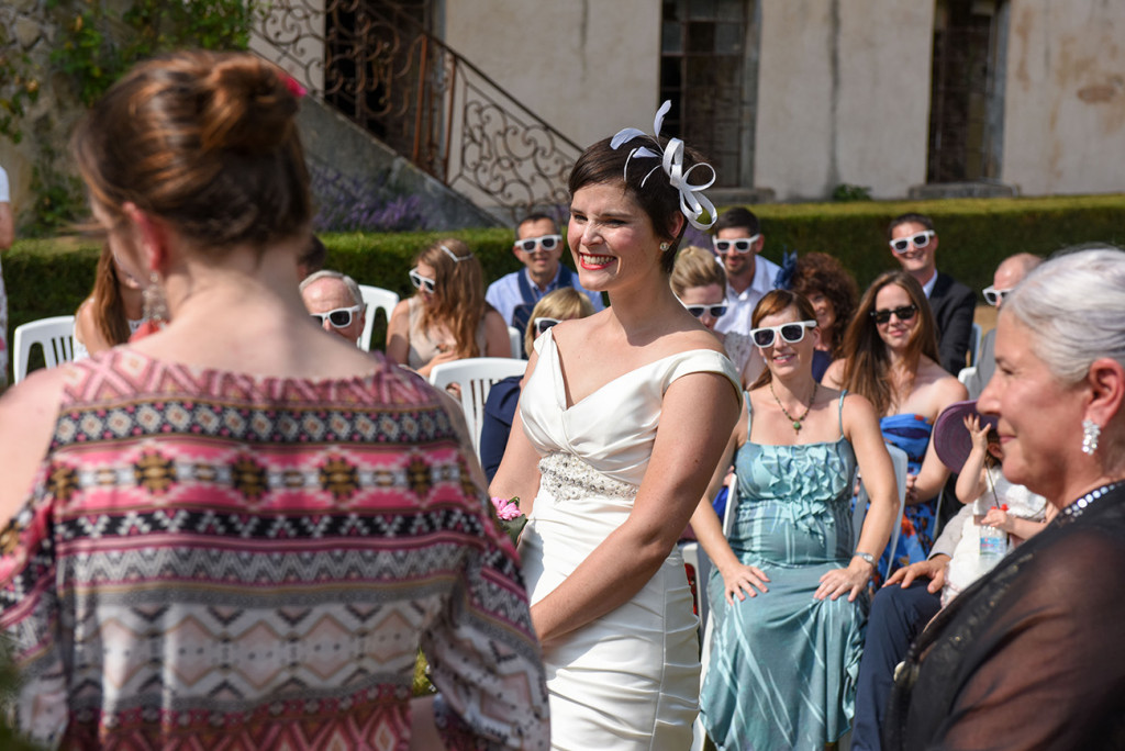 Bride smiling as Guests onlook the Outdoor French Wedding in Pranemoux Castle France