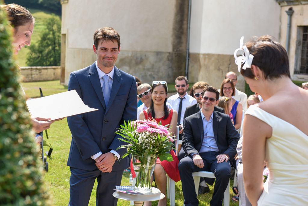 The groom smiles at the bride at their Outdoor French Wedding in Pranemoux Castle France
