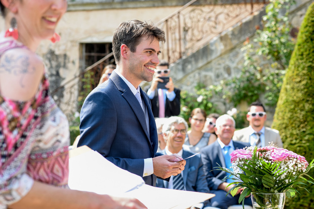 Groom smiles at the altar at his Outdoor French Wedding in Pranemoux Castle France
