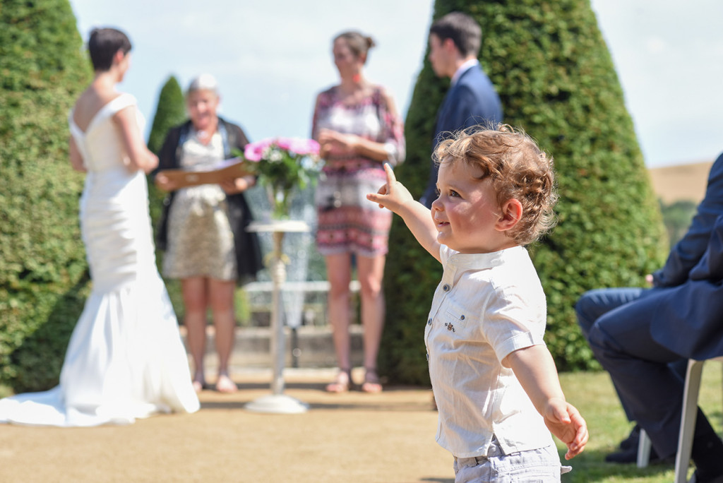 Baby boy points at couple at the altar at their outdoor French Wedding in Pranemoux Castle France