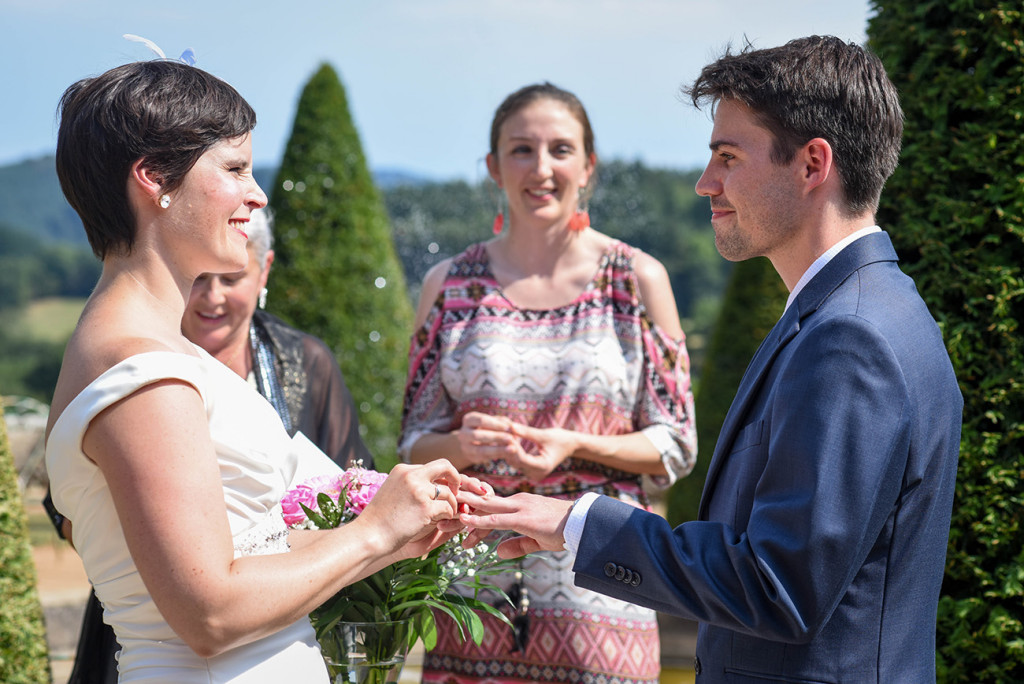 The couple exchanges rings at their outdoor French Wedding in Pranemoux Castle France
