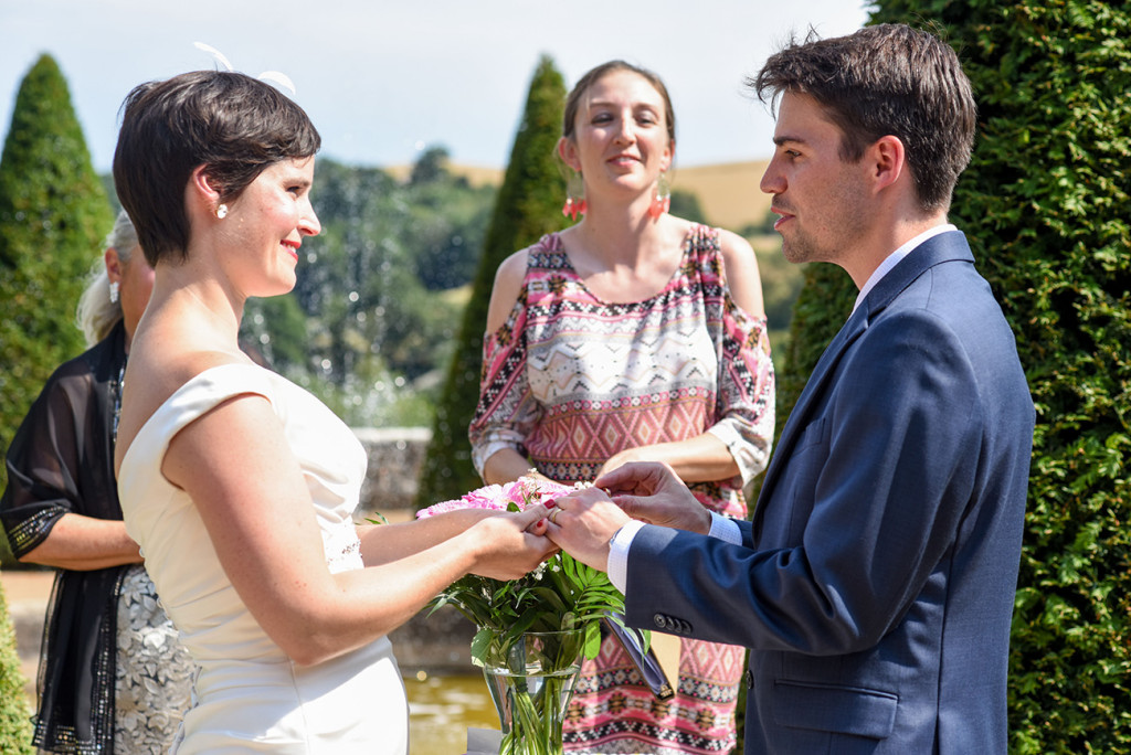 Couple exchanging rings at their outdoor French Wedding in Pranemoux Castle France
