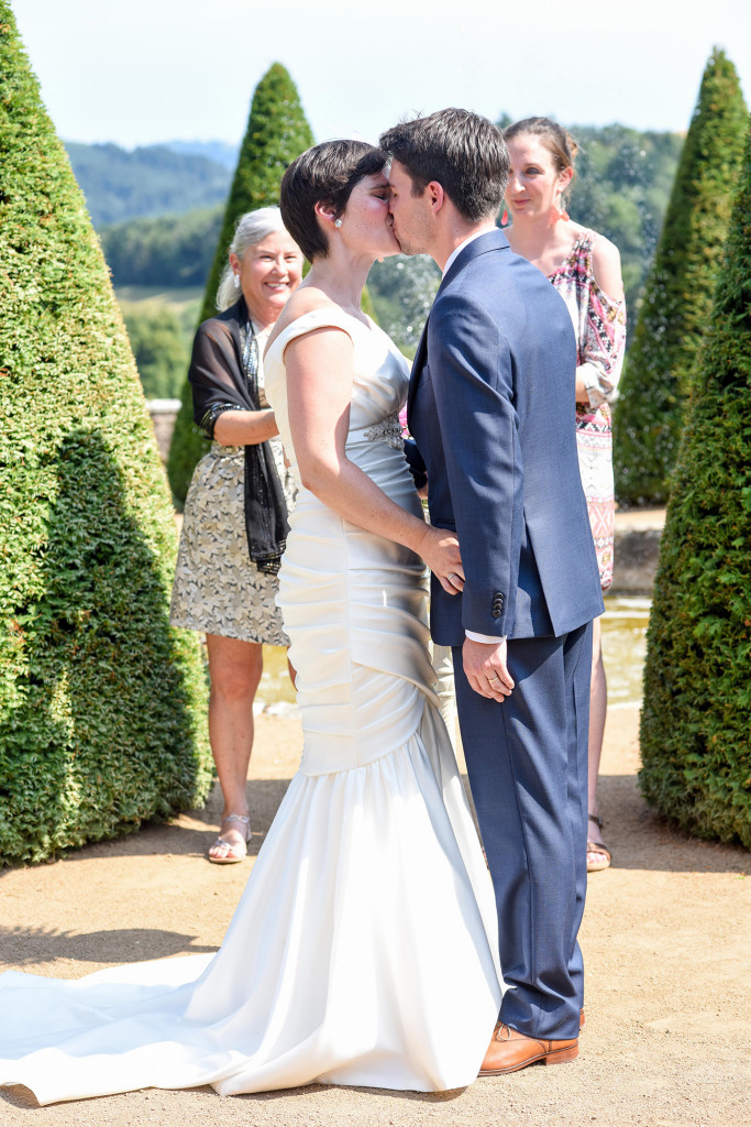 The couple kiss at the altar at their outdoor French Wedding in Pranemoux Castle France