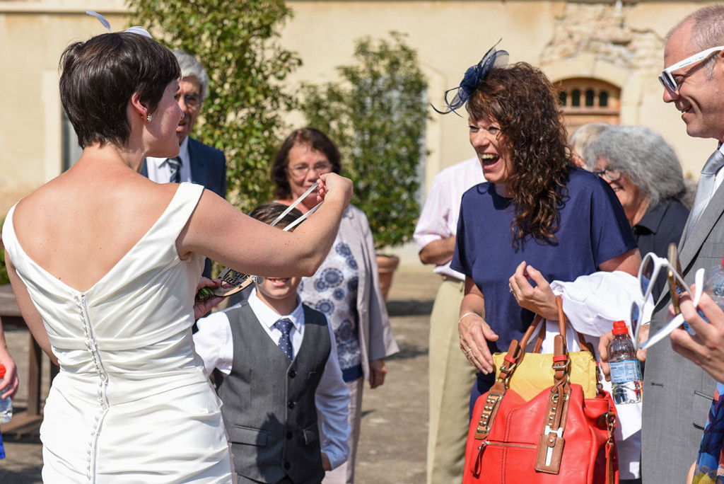 Bride laughs with friends at her outdoor French Wedding in Pranemoux Castle France