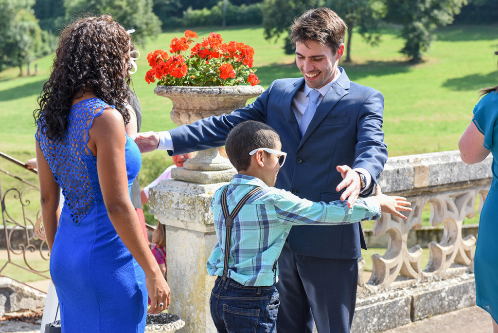 Groom hugs young friend at his outdoor French Wedding in Pranemoux Castle France