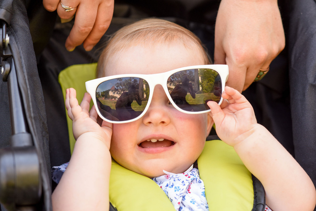 Funny baby with oversize sunglasses at outdoor French Wedding in Pranemoux Castle France
