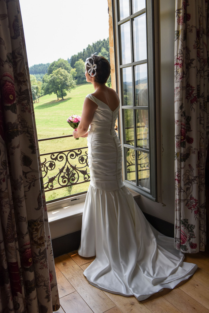 French Bride gazing out of the window at the Pranemoux Castle France