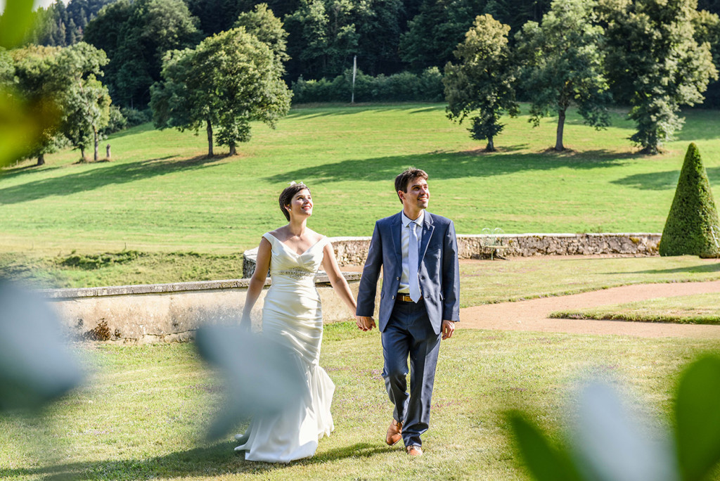 Newly married couple hand-in-hand for photoshoot at outdoor French Wedding in Pranemoux Castle France