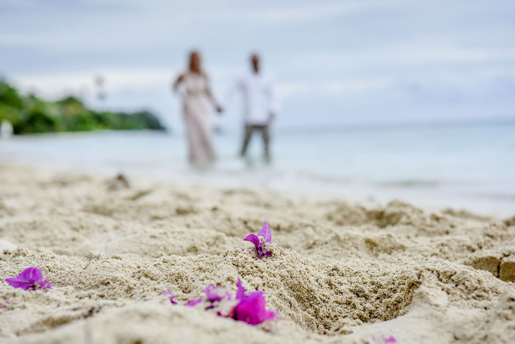 The pink petals in the foreground as the couple walks in the background family Beach Wedding on Malolo Island, Plantation Island Resort, Fiji Wedding Anais : Photographer