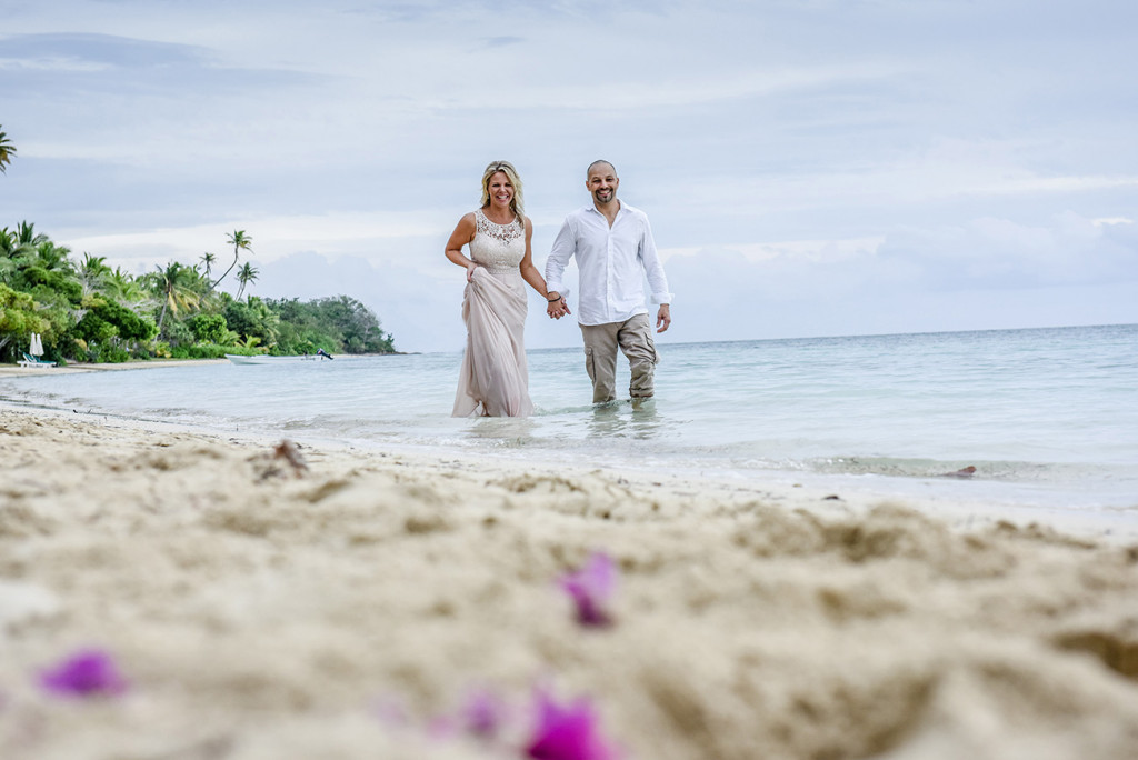 Bride and groom walk in the sea at family Beach Wedding on Malolo Island, Plantation Island Resort, Fiji Wedding Photographer