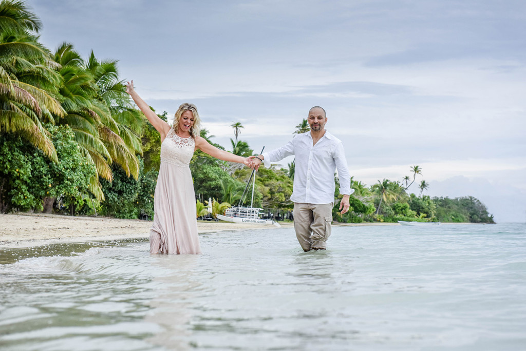 The bride and groom smile at the Fijian wedding photographer as they wade in the sea at family Beach Wedding on Malolo Island, Plantation Island Resort,