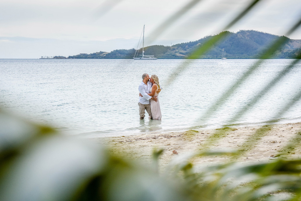 The bride and groom kiss at the shores of the sea at their family Beach Wedding on Malolo Island, Plantation Island Resort, Fiji Wedding Photographer