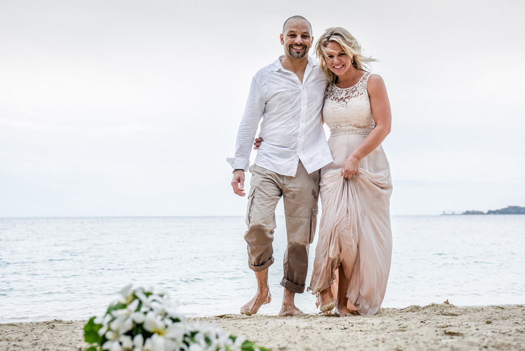 Bride and groom walk oan sea shore with white flower bouquet in foreground, in Fiji Wedding Photographer