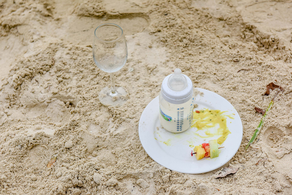 The empty plate that carried the baby's snacks for the The bride laughs with her son by the sea at her family Beach Wedding on Malolo Island, Plantation Island Resort, Fiji Wedding Photographer