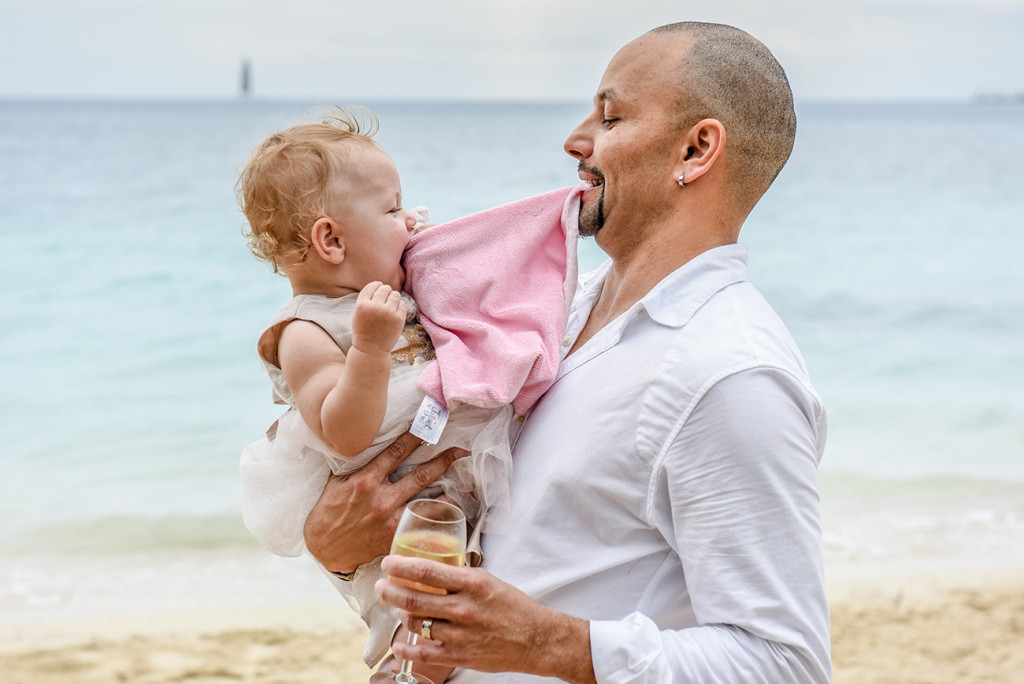 The groom plays with his daughter at his family Beach Wedding on Malolo Island, Plantation Island Resort, Fiji Wedding Photographer