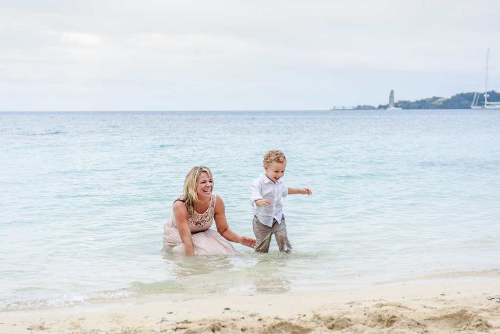 The bride and her son play in the water at their Beach Wedding on Malolo Island, Plantation Island Resort, Fiji Wedding Photographer