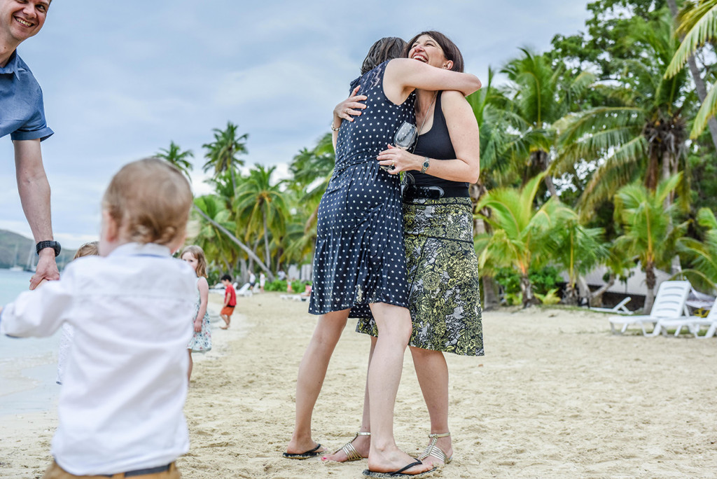 One of the wet guests hugs a friend, on Plantation Island Resort, Fiji Wedding Photographer