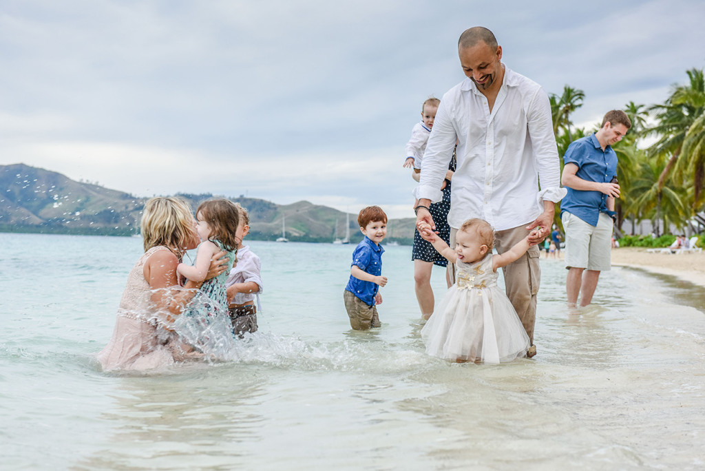 The groom supports his baby girl as she wads in the water at their wedding on Malolo Island, Plantation Island Resort, Fiji Wedding Photographer