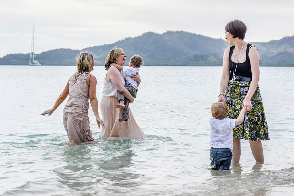 The bride plays with her babies in the sea at Malolo Island, plantation island resort, Fiji Wedding Photographer