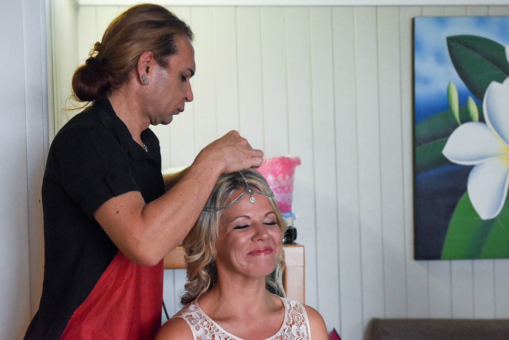 The Hair & MU artist places a traditional headchain on the bride for her Fiji beach wedding