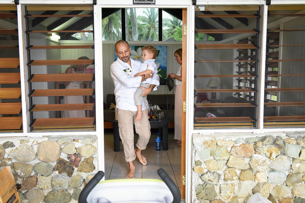 The groom carries his son before their family Beach Wedding on Malolo Island, Plantation Island Resort, Fiji Wedding Photographer