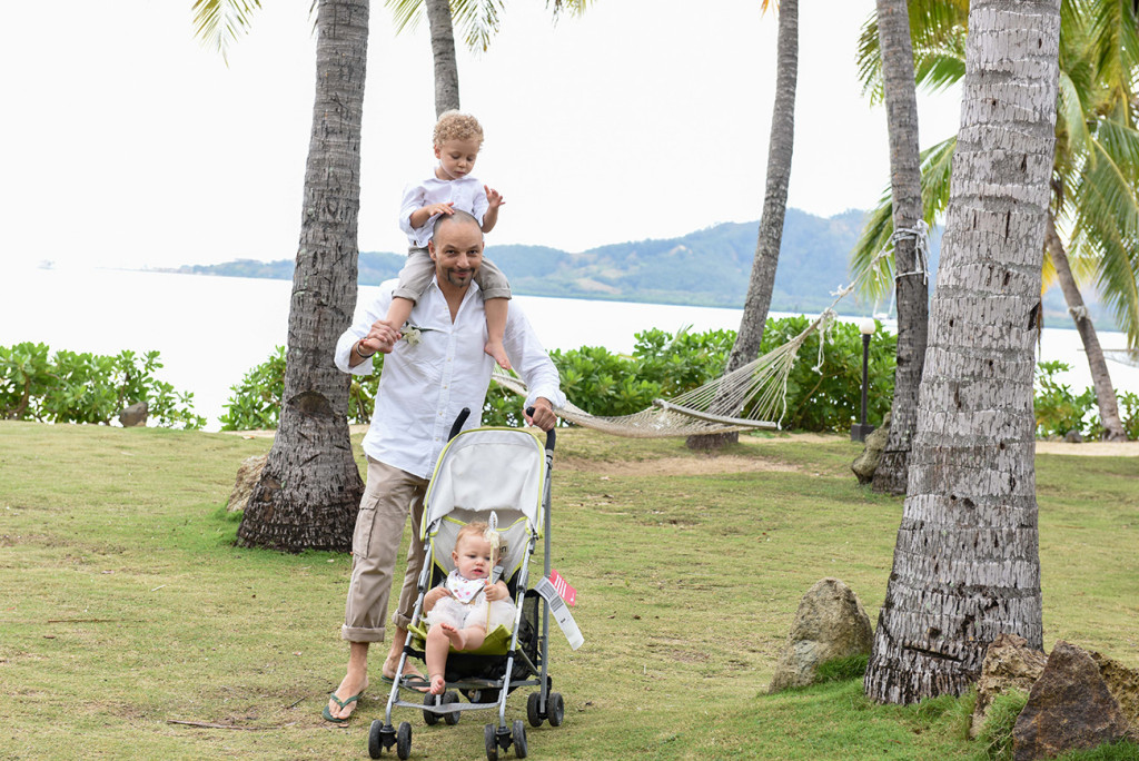 The groom walks his son and daughter on the hotel garden before their amily Beach Wedding on Malolo Island, Plantation Island Resort, Fiji Wedding Photographer
