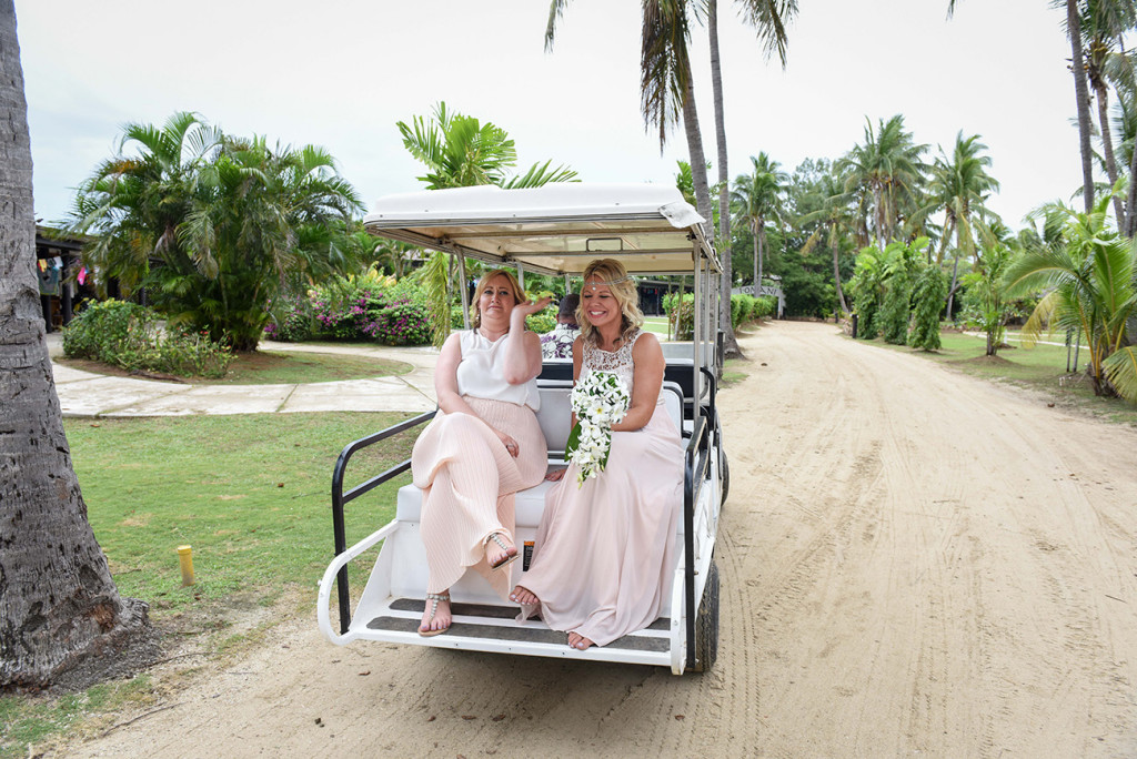 Bride and bridesmaid in golfcart arriving at the venue of the family Beach Wedding on Malolo Island, Plantation Island Resort, Fiji Wedding Photographer