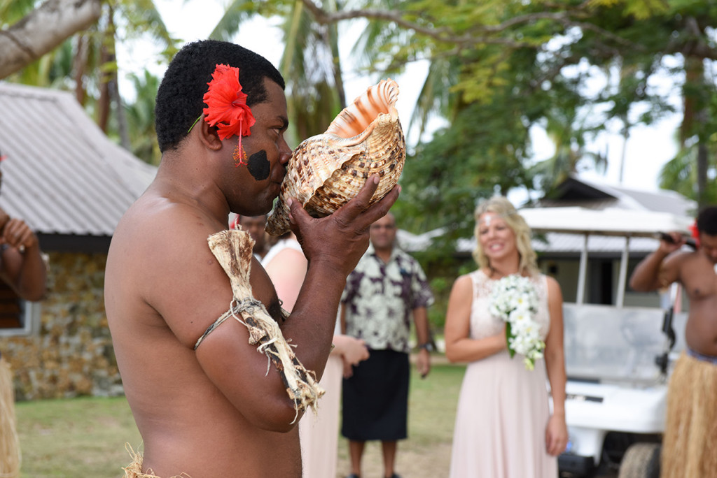 A traditional Fiji dancer blows into a shell at the family Beach Wedding on Malolo Island, Plantation Island Resort, Fiji Wedding Photographer