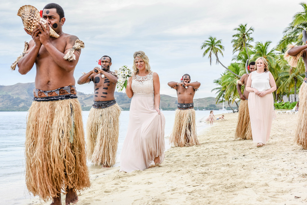 The bride walks alongside traditional Fiji dancers as they perform an entrance piece at her family Beach Wedding on Malolo Island, Plantation Island Resort, Fiji Wedding Photographer