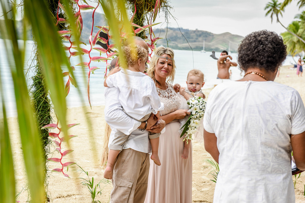 The family watch from the altar of their wedding with Fijian warriors in the background