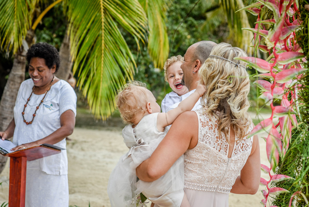 The family shares a laughter as a Fijian celebrant officiates the family Beach Wedding on Malolo Island, Plantation Island Resort, Fiji Wedding Photographer