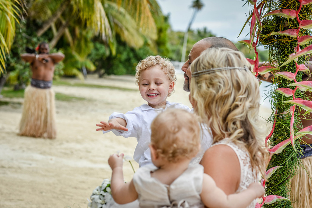 The young son reaches out to his sister at their parents family Beach Wedding on Malolo Island, Plantation Island Resort, Fiji Wedding Photographer