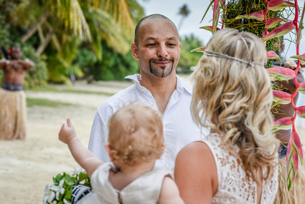 Groom smiles at his wife at the altar of their family Beach Wedding on Malolo Island, Plantation Island Resort, Fiji Wedding Photographer