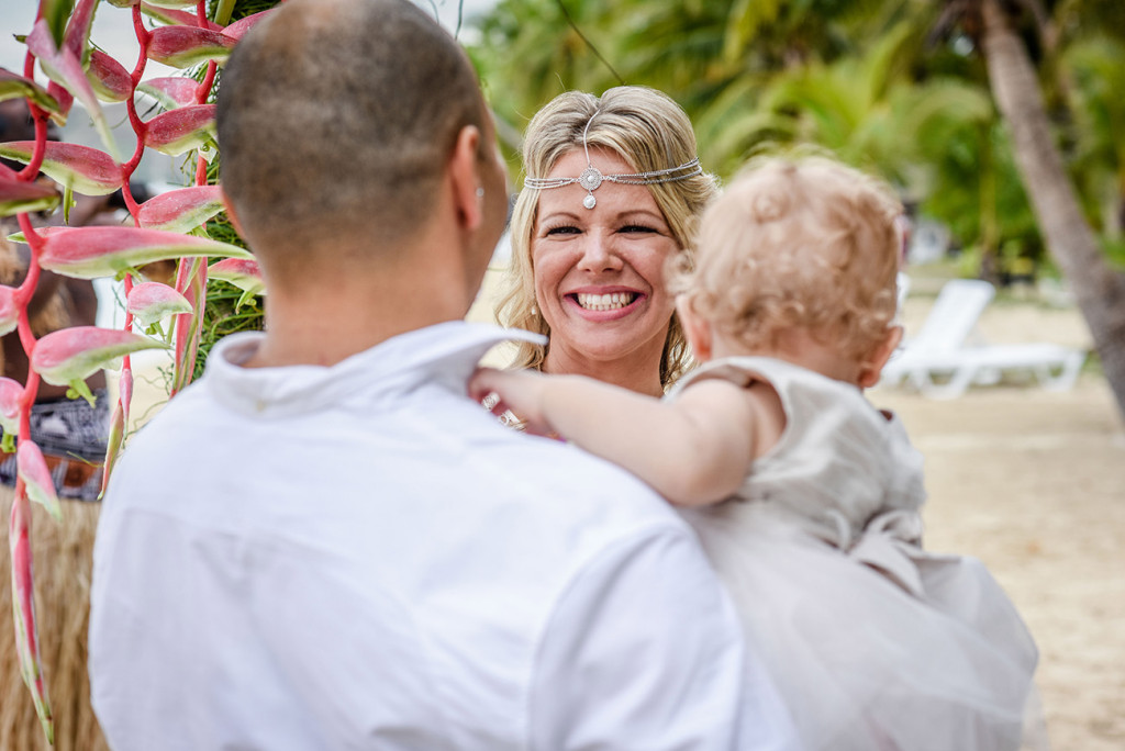 The bride smiles at her husband at the altar of their family Beach Wedding on Malolo Island, Plantation Island Resort, Fiji Wedding Photographer