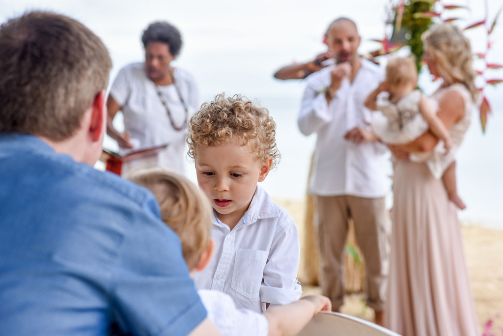 The couple's son plays in the foreground at their parents' family Beach Wedding on Malolo Island, Plantation Island Resort, Fiji Wedding Photographer