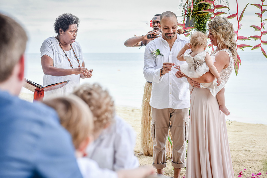 The couple exchanges rings at the altar of their family Beach Wedding on Malolo Island, Plantation Island Resort, Fiji Wedding Photographer