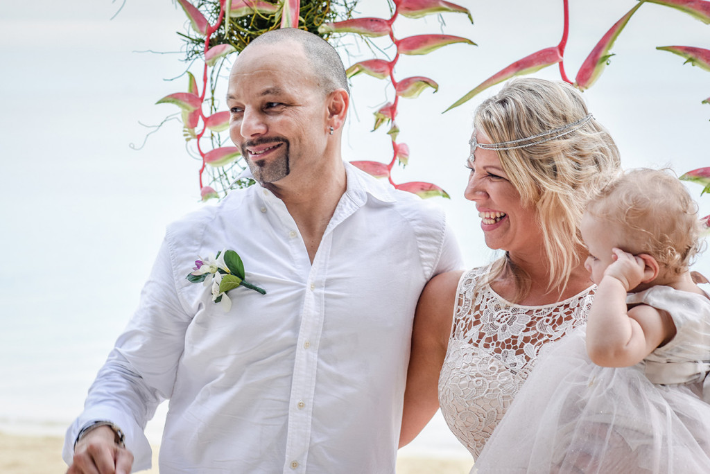 Happy bride, groom and daughter at the altar at their family Beach Wedding on Malolo Island, Plantation Island Resort, Fiji Wedding Photographer