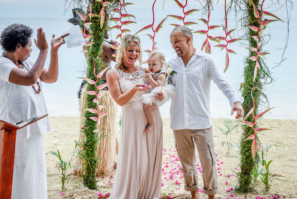 Bride, groom and daughter at the altar at their family Beach Wedding on Malolo Island, Plantation Island Resort, Fiji Wedding Photographer