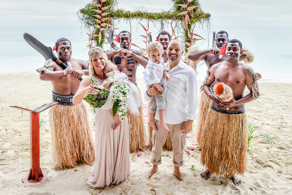 The couple pose with traditional Fijian dancers at their family Beach Wedding on Malolo Island, Plantation Island Resort, Fiji Wedding Photographer