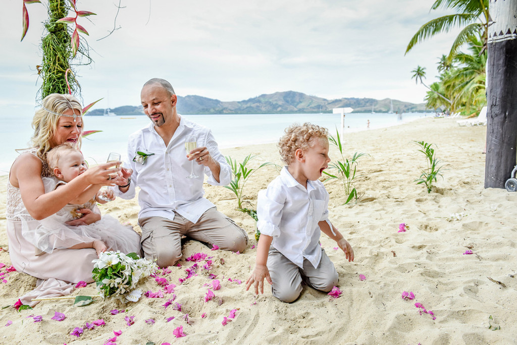 The wedded family plays in the sand at the family Beach Wedding on Plantation Island, Fiji Wedding Photographer