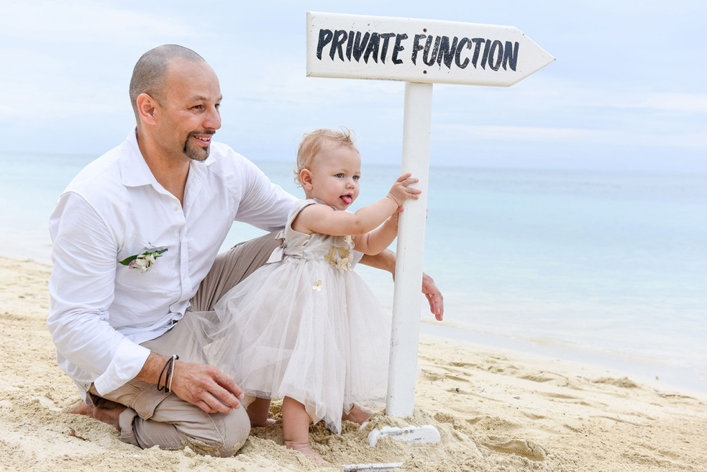 The couple's daughter holds up the Private function sign at the family Beach Wedding on Malolo Island, Plantation Island Resort, Fiji by Anais Wedding Photographer