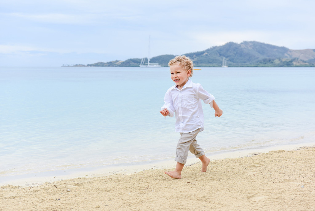 The young boy runs happy and free on the seashore at family Beach Wedding on Malolo Island, Plantation Island Resort, Fiji Wedding Photographer
